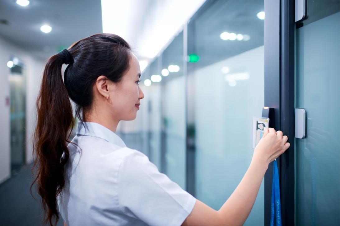 Woman using key card to open office door